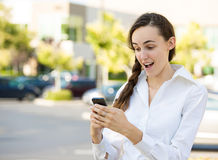 Shocked woman reading text message on smart phone Royalty Free Stock Photos