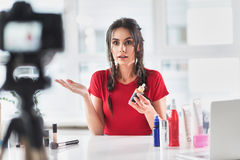 Shocked woman recording video blog about cosmetics Royalty Free Stock Image