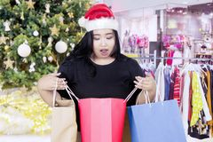 Shocked woman with shopping bag in the mall. Image of fat woman looks shocked while opening a shopping bag and standing near Christmas tree in the mall Royalty Free Stock Image