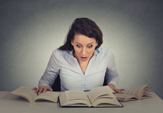 Shocked woman sitting at desk with many opened books reading Royalty Free Stock Images