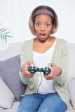 Shocked woman sitting on sofa playing video games Stock Image