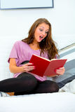 Shocked woman sitting on sofa and reading book Royalty Free Stock Photo