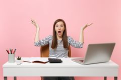Shocked woman spreading hands using calculator writing notes with calculations sit, work at office with pc laptop. Isolated on pastel pink background royalty free stock image