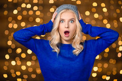 Shocked woman standing over holidays lights background Stock Photography