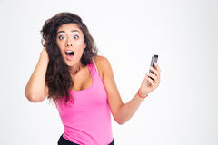 Shocked woman standing with smartphone Stock Image