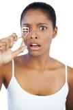 Shocked woman using curler for her eyelash Stock Photo