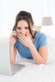 Shocked woman using mobile phone and laptop in bed Stock Images
