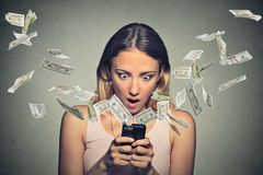 Shocked woman using smartphone dollar bills flying away from screen