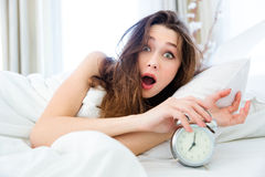 Shocked woman waking up with alarm Royalty Free Stock Photo
