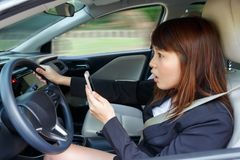 Shocked woman watching video or text to someone with smart phone. While driving fast a car distracted Stock Image