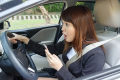 Shocked woman watching video or text to someone with smart phone. While driving fast a car distracted Royalty Free Stock Photos