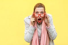 Shocked woman wearing coat, pink scarf, opening mouths , having Stock Photo