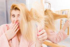 Shocked woman wearing dressing gown brushing her hair Stock Photos
