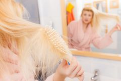 Shocked woman wearing dressing gown brushing her hair Royalty Free Stock Photography