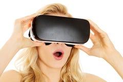 Shocked woman wearing virtual reality goggles Stock Photos