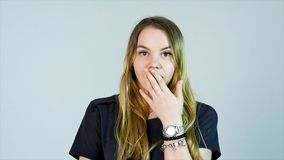 Shocked woman. Young woman touching face with hands and staring at camera while standing against white background.  Stock Photos