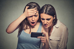 Shocked women displeased young girls looking at mobile phone Royalty Free Stock Photos