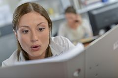 Shocked woman with folder royalty free stock image
