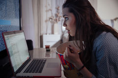 Shocked wondered woman using laptop and eating popcorn Stock Images