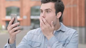 Shocked, wondering young man using smartphone stock video