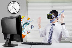 Shocked worker with fishes on monitor. Young businessman looks shocked with fishes coming out from the monitor, wearing goggles and snorkel in the office Royalty Free Stock Images