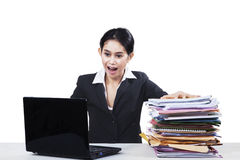 Shocked worker with paperwork and laptop Stock Image