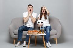 Shocked worried couple woman man football fans cheer up support favorite team with soccer ball, expressive gesticulating royalty free stock photos