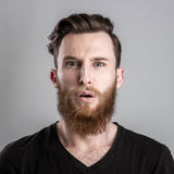 Shocked and worried young man isolated on gray backround Stock Photo