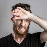 Shocked and worried young man isolated on gray backround Royalty Free Stock Images