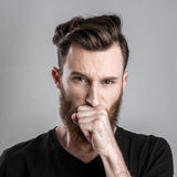 Shocked and worried young man isolated on gray backround Royalty Free Stock Photos