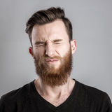 Shocked and worried young man isolated on gray backround Stock Photos