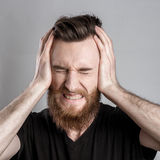 Shocked and worried young man isolated on gray backround Stock Photography