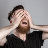 Shocked and worried young man isolated on gray backround Stock Image