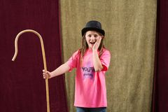 Shocked young actress wearing hat. Shocked young actress places hand on face and holds staff with the other Royalty Free Stock Image