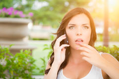 Shocked Young Adult Female Talking on Cell Phone Outdoors Stock Photography