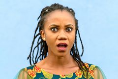 Shocked young African American woman. With dreadlock braids staring at the camera with a look of wide eyed horror isolated on blue stock photos