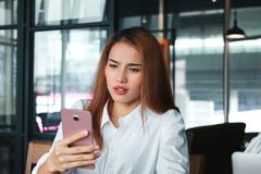 Shocked young Asian business woman with mobile smart phone in office. Internet of things concept stock images