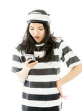 Shocked young Asian woman text messaging on a mobile phone in prisoners uniform. Young attractive Asian woman in her 20's shot in studio isolated on a white stock image