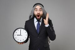 Shocked young bearded arabian muslim businessman in keffiyeh kafiya ring igal agal classic suit isolated on gray