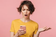 Shocked young beautiful woman posing isolated over pink wall background using mobile phone royalty free stock photography