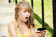 Shocked young blond reading text. Young woman, teenager girl or student shocked at what she is reading on her cell phone, perfect for online intimidation or Stock Images