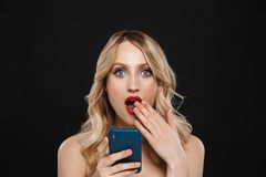 Free Shocked Young Blonde Woman With Bright Makeup Red Lips Posing Isolated Over Black Wall Background Using Mobile Phone Stock Images - 153979474