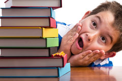 Shocked young boy looking at his textbooks. Shocked young boy looking at his stack of textbooks for elementary school with his hands to his cheeks and mouth open Royalty Free Stock Photos