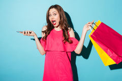 Shocked young brunette woman holding shopping bags and mobile phone. Stock Images