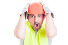 Shocked young builder holding his head looking desperate Stock Photography