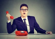 Shocked business man receiving bad news on the phone royalty free stock image