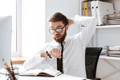 Shocked young businessman looking at watch. Stock Photos