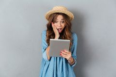 Shocked young caucasian woman chatting by tablet Royalty Free Stock Photography