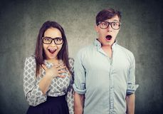 Shocked young couple in glasses. Couple of nerd men and women in glasses standing together and looking amazed on gray background Stock Photography