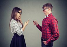 Shocked young couple using smart phones. Looking stunned and amazed stock photos